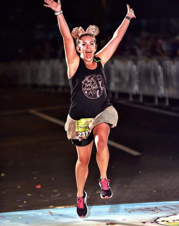 Sarah Bergman, a rundisney travel agent, crossing the finish line at a race