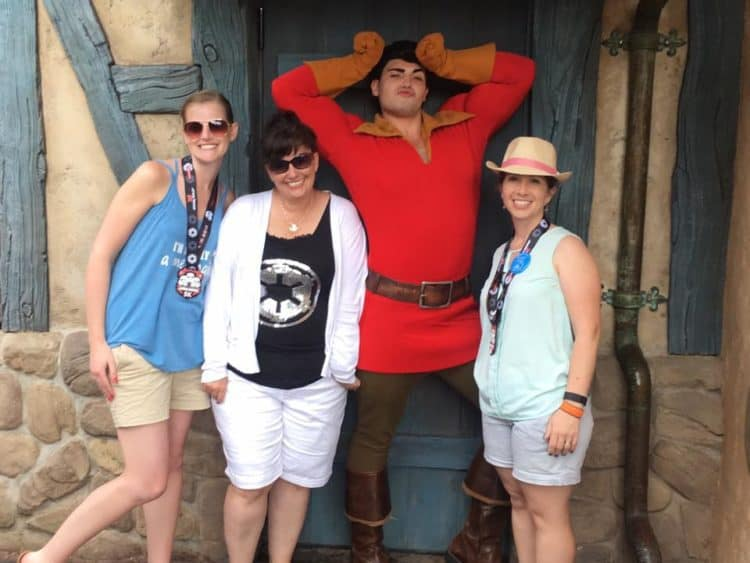 Gaston meet and greet after a runDisney race. 3 girls with medals and gaston