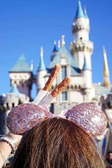 rose gold minnie ears and churros at disneyland in front of castle